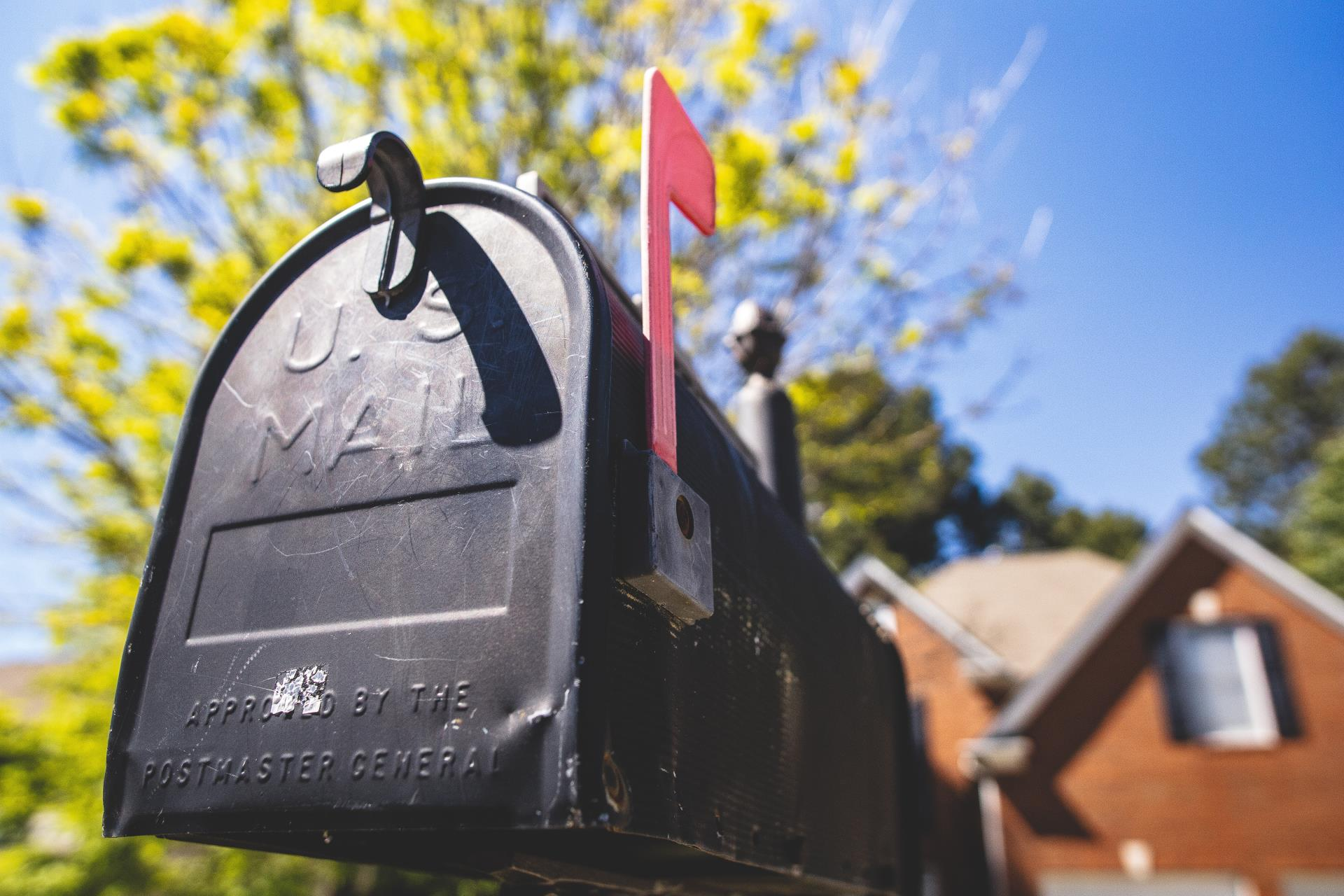 Black mailbox United States Postal Service with Red Flag and house in the background